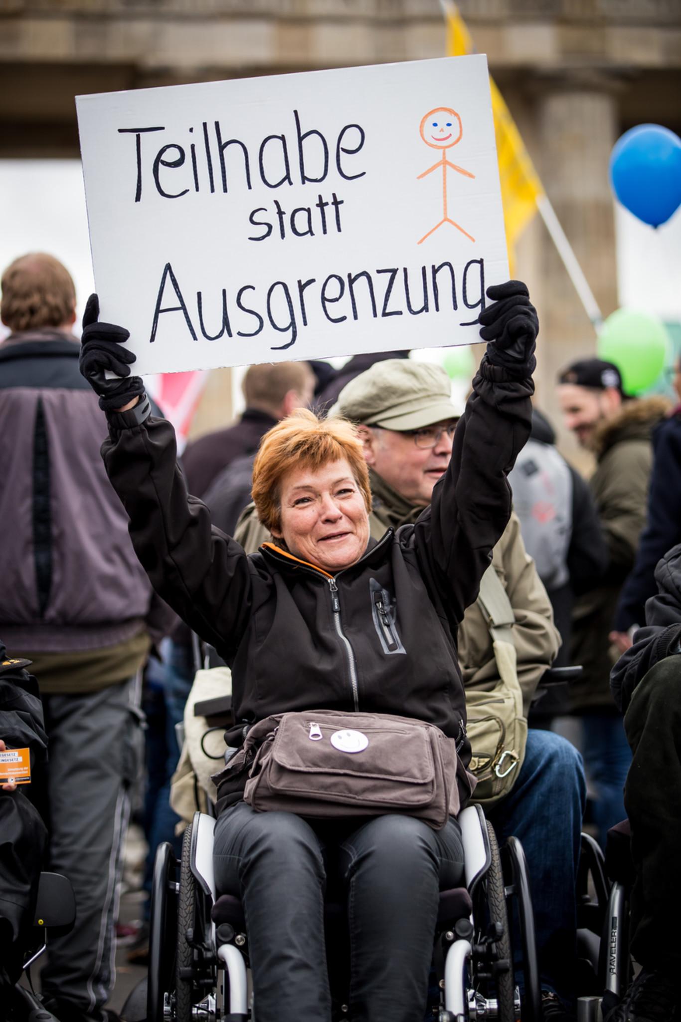 Frau mit Rollstuhl protestiert und hält Banner: Teilhabe statt Ausgrenzung