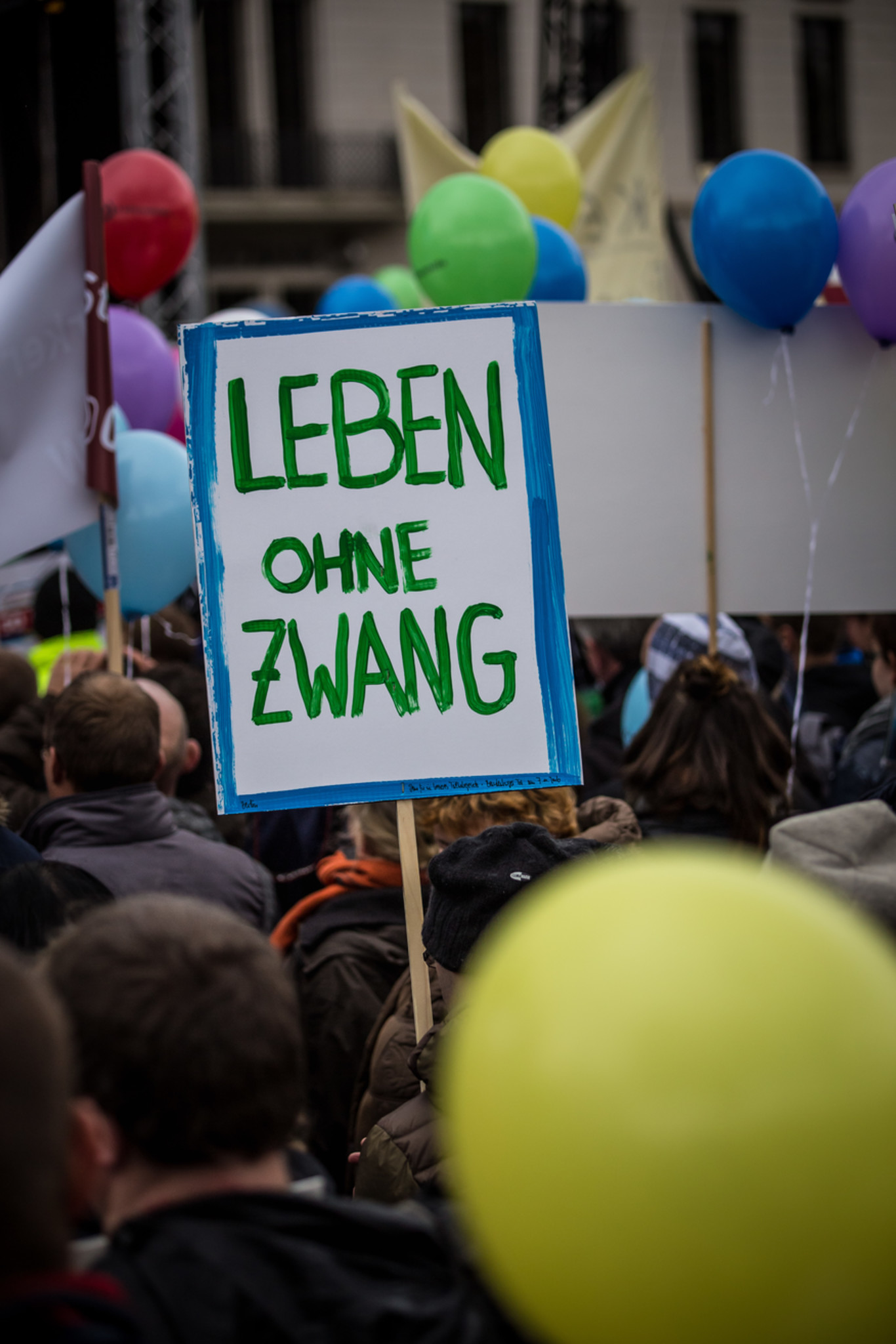 """Protestierende Menschen; Schild """"Leben ohne Zwang"""""""